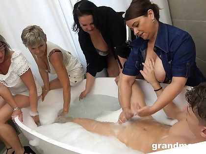 Taking a bath dude is treated with random solid BJ by mature sluts
